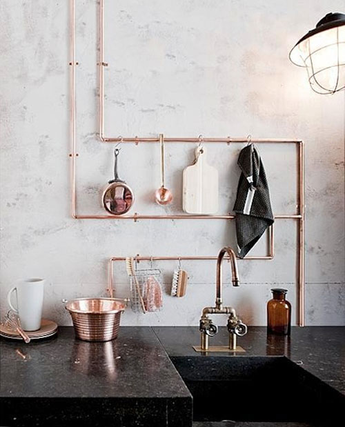 DIY Pot Rack Ideas: In a small kitchen, exposed copper pipe doubles as storage for pots and other items.