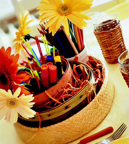 Kids Thanksgiving Table Ideas: Stack several baskets filled with crayons, markers, and colored pencils. Then decorate them with a few floral stems and use them as a centerpiece. Cover the table with craft paper and the little ones will stay busy.