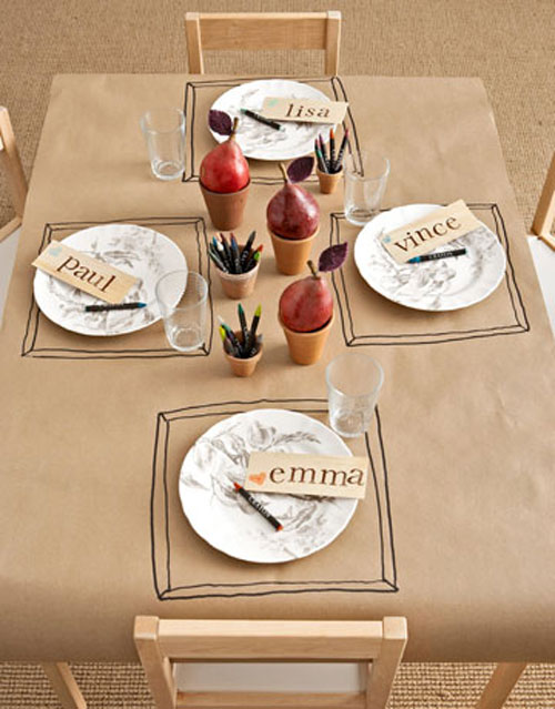 Kids Thanksgiving Table Ideas: For the youngest guests, cover a table with craft paper. Then set out pots of crayons for tic-tac-toe games or doodling. Make each child feel special by making them a place card.