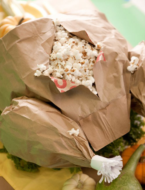 Kids Thanksgiving Table Ideas: Make a paper bag turkey filled with popcorn. The body is made out of a large grocery bag and the legs are made from small lunch bags.