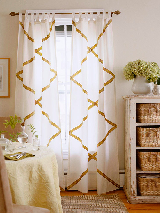 "No-Sew Curtains: Bring the ""wow-factor"" to a room by accenting hanging tab-top panels with ribbon and rick rack. Natural colors and textures will help keep the pattern from being overwhelming. Before applying trim, carefully measure out the pattern and mark accordingly. Each X extends from side to side and repeats three times from the top to the bottom. The ribbon is glued down first, then the rickrack is glued on top of it. Finally, a button is glued at each intersection. To finish off the edges, cut the ribbon 1 inch longer than needed, wrap it around the edge of the curtain and glue it to the back."