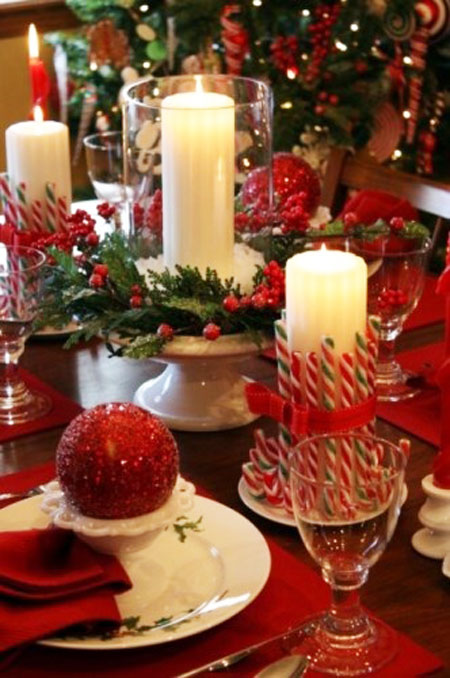 Christmas Table Ideas Using Red and White: What's Christmas without candles? Plain pillar candles are given a sweet treatment by adding striped candy canes tied with ribbon. Glue the unwrapped candy canes in place; then tie a decorative ribbon around it.