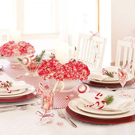 Christmas Table Ideas Using Red and White: Red and white carnations placed on a striped runner take center stage on this candy cane themed table. Red and white pipe cleaners are used to create candy cane shaped napkin rings. Fill small glasses with more candy canes, then tie with red ribbon for an extra punch of color.