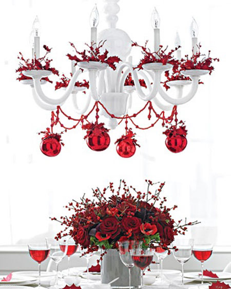 Christmas Table Ideas Using Red and White: To bring even more holiday cheer to the table, drape a white chandelier in red beads and ornaments.