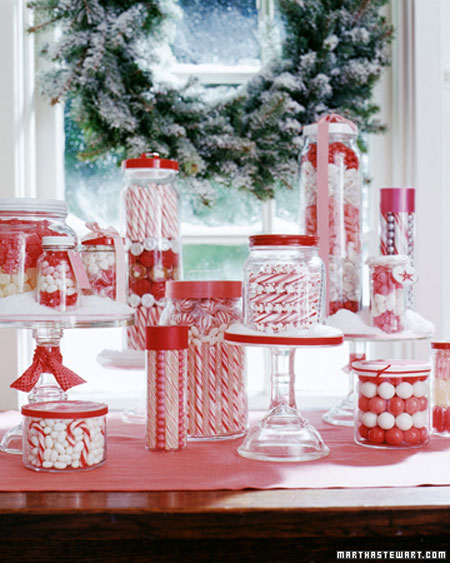 Christmas Table Ideas Using Red and White: For a different twist on a centerpiece, fill jars with red and white candy. Buy inexpensive glass jars or make your own using glass jars you've saved from jelly, olives, etc. After dinner, you can give the filled jars out as gifts.