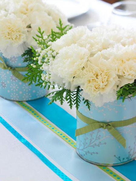 Christmas Centerpieces: Cover coffee cans with wrapping or craft paper and tie with a ribbon. Then fill them with inexpensive carnations. Accent with some baby's breath and a little greenery.