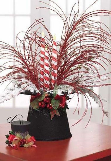 Christmas Centerpieces: A black top hat is the perfect base for creating a whimsical centerpiece. It's complete with candy cane striped candles and feathery plumes. I'd use the little top hat as place cards and let everyone take theirs home as a gift.