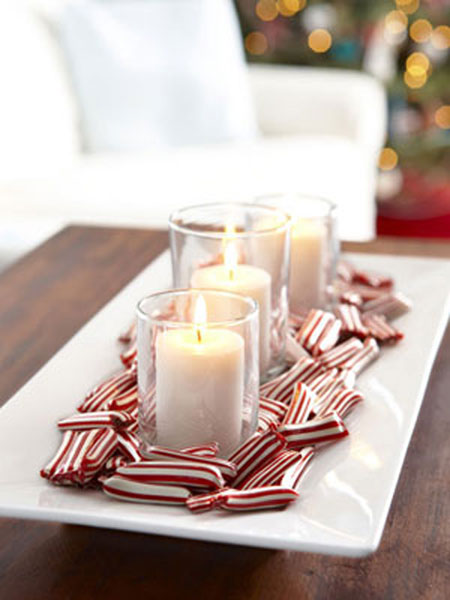 Christmas Centerpieces: Create a candy dish centerpiece. Put white pillar candles in clear glass holders. Then place them on a long sleek white tray and surround them with red and white peppermints. This not only looks good, but it tastes good too.