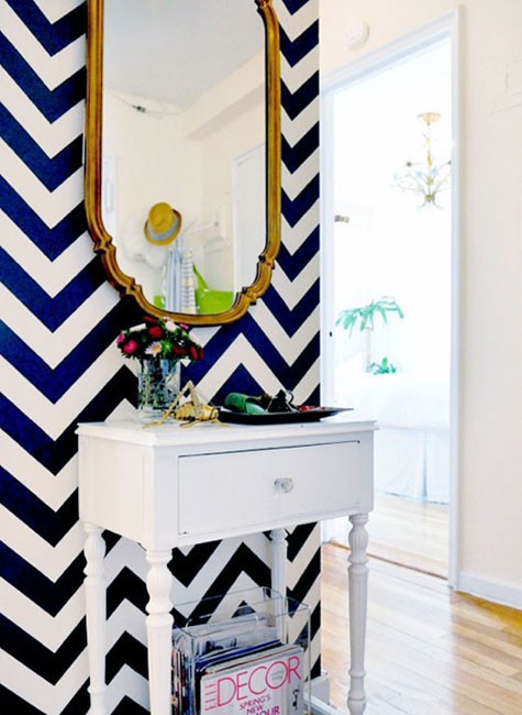 Entryway Ideas: A blue and white chevron pattern helps define this entryway and gives it tons of personality. A simple cabinet painted in white provides storage, while a vintage gold-framed mirror dresses things up.