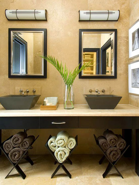 Bathroom Towel Storage Ideas: Turn the open area below a modern sink into useful storage space. To create storage, roll up towels and place them in contemporary wooden magazine racks.