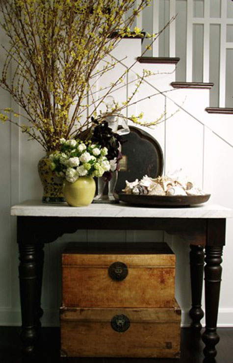 Entryway Ideas: A tall flower arrangement gives height to this entryway vignette as it follows the lines of the staircase. Two vintage trunks make for great storage beneath the table, add a contrasting color and texture, and anchor the design.