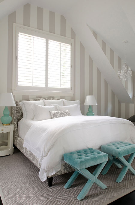 Turquoise Room Ideas: The soft turquoise of the lamps is repeated in the tufted velvet benches at the foot of the bed. Grey and white stripes visually expand the height of the room.