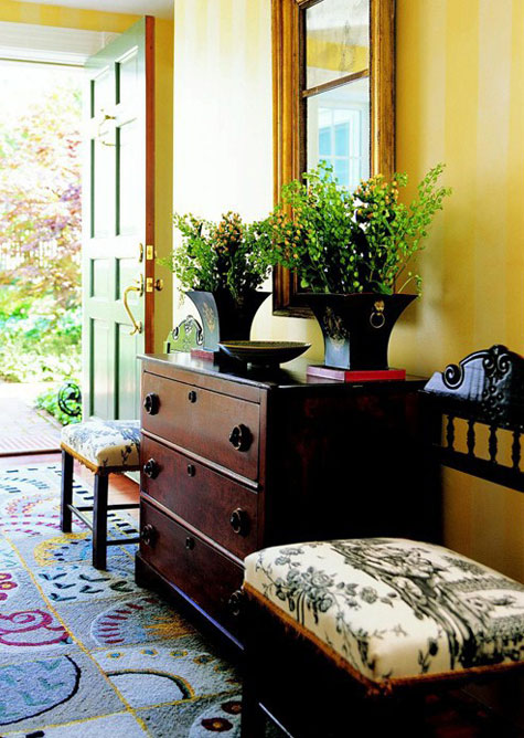 Entryway Ideas: Yellow tone-on-tone striped walls add interest to this entryway without be overpowering. Mixing contemporary patterns with antique and traditional elements gives it warmth and makes it comfortable. Notice the use of balanced design beginning with the mirror and the chest, flanked by two matching plants and chairs.