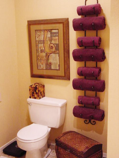 Bathroom Towel Storage Ideas: If you like the idea of using a wine rack for towel storage but don't have the floor space, opt for a wall hanging model. This particular style holds four sets of bath and hand towels while taking up very little space.