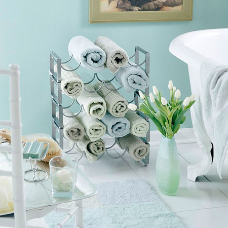 Bathroom Towel Storage Ideas: Rolled up towels fit perfectly in a standing wine rack. This is a great storage solution and keeps towels within easy reach. It's also very decorative. Choose towels in colors to coordinate with your bathroom decor.