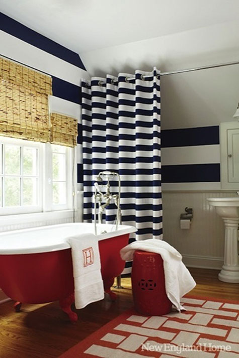 Red Rooms: Decorating With the Color Red - A red claw-foot tub is the centerpiece in this navy blue and white nautical style bathroom